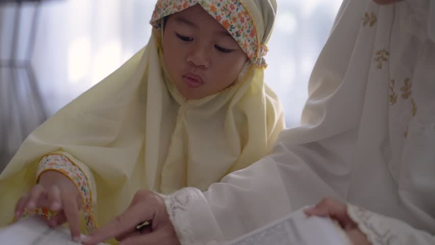 Muslim parent and daughter reading quran after praying together | Shutterstock HD Video #1029243464