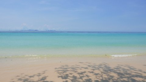 Gentle waves wash onto a deserted beach on a beautiful tropical island paradise. Shadows of leaves on trees that line the shore. Clear water in shades of blue and a clear warm sky.