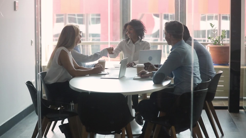 Multi-ethnic business partners gathered negotiate in boardroom behind closed doors view through glass, entities parties after discuss details of agreement signing contract shake hands feels satisfied