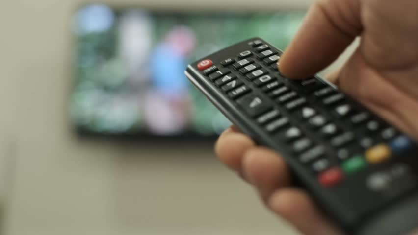 Man switches channels on the TV using the remote. | Shutterstock HD Video #1029358964