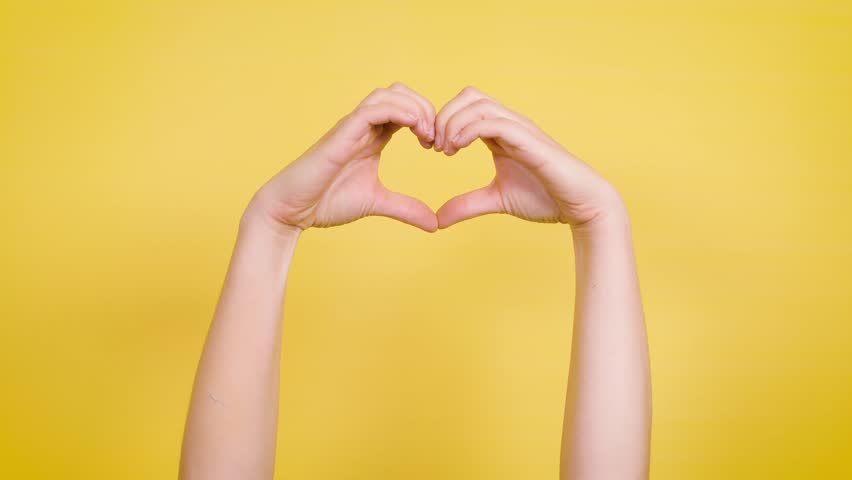 Hands make heart symbol against yellow backdrop. | Shutterstock HD Video #1029397364