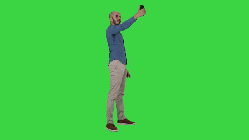 Selfie time! Handsome young man taking selfie with his phone on a Green Screen, Chroma Key. #1029439394