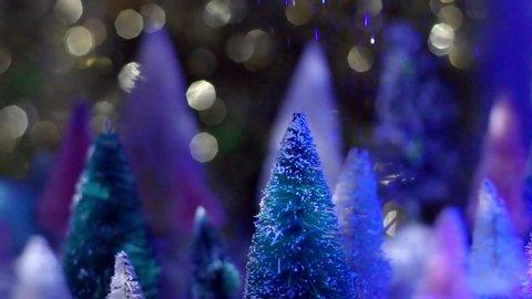 Slow Motion nighttime shot of glitter snow falling on top of vintage bottle brush tree.