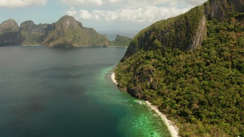 aerial view tropical lagoon with sandy beach surrounded by cliffs. El nido, Philippines, Palawan. Seascape with tropical rocky islands, ocean blue water. Summer and travel vacation concept
