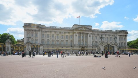 London, UK - June 22, 2018: Buckingham Palace with many people tourists crowd walking or standing taking photos pictures photographing during summer, sunny day and clouds with sky