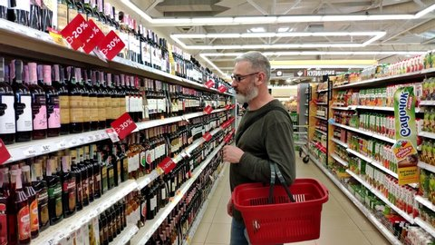KHARKIV, UKRAINE - April 1, 2019: adult man with a beard chooses wine on a shelf with a glass case in the Ukrainian supermarket, discounts on wine