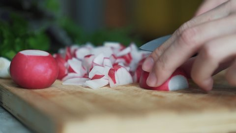 Close up woman hands with knife cutting radishes on wooden board. Cook prepares vegetable salad. Concept of natural and healthy food
