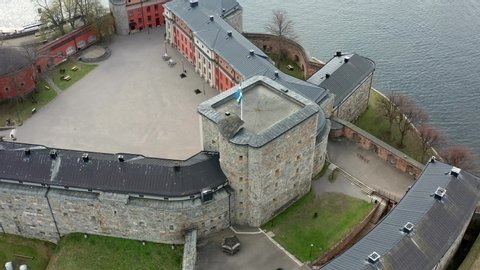 Swedish flag on Vaxholm fortress in circling aerial drone shot. Historic fortification on the island of Vaxholmen in the Stockholm archipelago. Military fort.