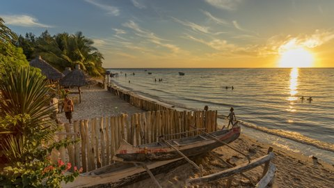 Sunset timelapse on the beach of Ifaty, Mangily, near Toliara / Tulear South West Madagascar. Tropical sandy beach, thatched huts, exotic vegetation, traditional wooden fishing boat and beautiful sky