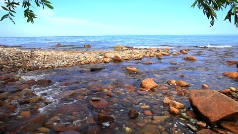 The shore of Lake Baikal on a sunny summer day. A small mountain river with clear transparent water flows into the lake. Natural water background