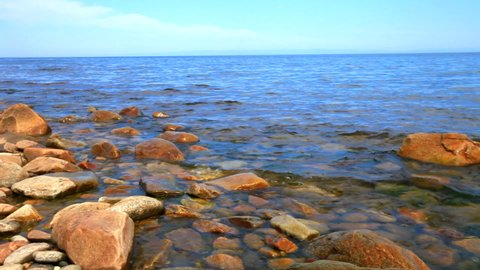 The shore of Lake Baikal on a sunny summer day. Natural water background