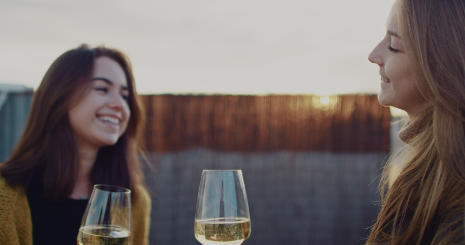 Two young beautiful girls drinking white wine with a city view during sunset. Slow Motion. Shot on RED digital cinema camera | Shutterstock HD Video #1029670784