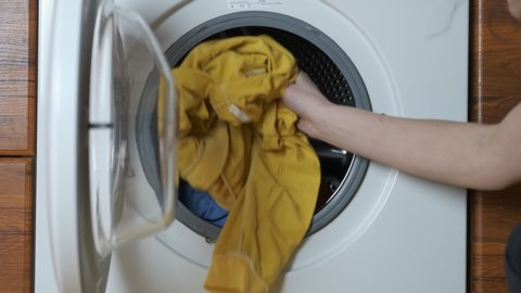 Washing clothes. Washer machines put dirty clothes.