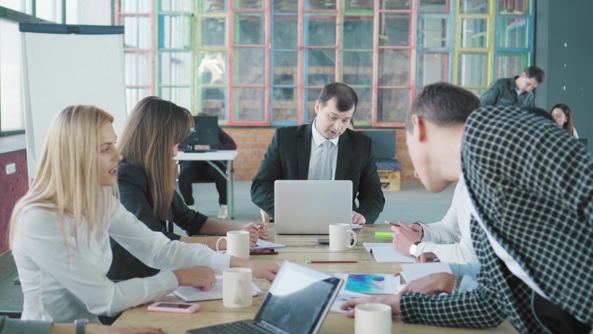 A business team is discussing a project at a large office table. Creative office interior. Coworking. Office workers | Shutterstock HD Video #1029684674