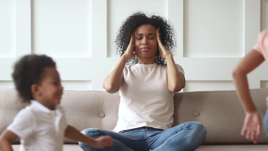 Stressed upset african american mom feeling migraine headache tired of too active kids running around, annoyed single black mother desperate about two difficult naughty children misbehaving at home