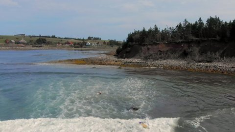 Cinematic drone / aerial footage ascending showing the beach, a bay, a couple of surfers and a few chalets in Kingsburg, Nova Scotia, Canada during summer season.