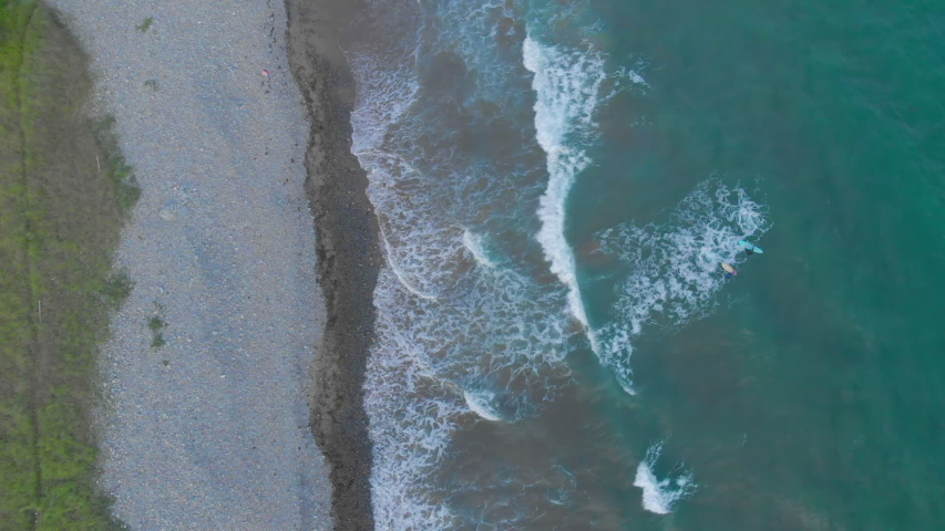 Cinematic drone / aerial discovery shot showing a couple of surfers and waves hitting the beach at Cole Harbour coast in Lawrencetown, Nova Scotia, Canada during summer season. | Shutterstock HD Video #1029735134