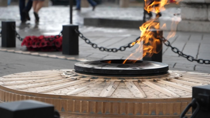 Slow motion fire memorial burning on overcast moody day in front of Arc De Triomphe, Paris, France | Shutterstock HD Video #1029749414