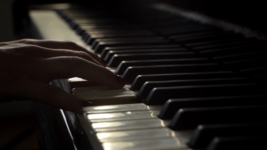 Woman pianist plays gentle classical music on a beautiful grand piano with one hand close-up in slow motion. Piano keys close up in dark colors. Student trains to play the piano #1029792554