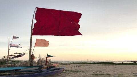 May 2019 in Rayong Thailand. Red warning flag flutters in the wind on a   beach to alert people not to swim because of strong winds and waves during the evening when the sunset.