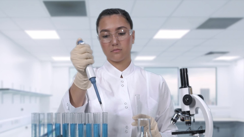 A female scientist examines a blue fluid sample using a micropipette and test tubes while sitting at a table in the newest medical laboratory. Slow motion | Shutterstock HD Video #1029888134