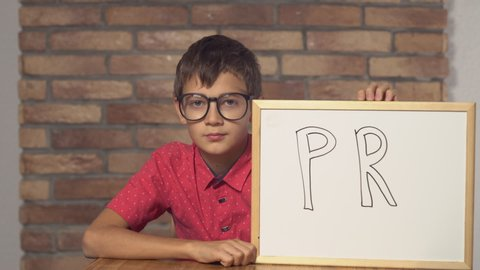 child sitting at the desk holding flipchart with lettering pr on the background red brick wall