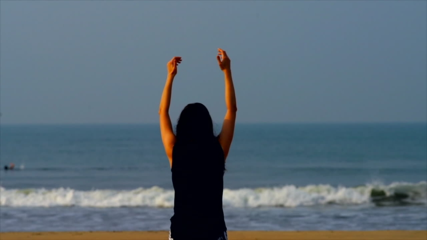 A young beautiful woman doing yoga on the beach near the ocean, close up, backside, slow motion | Shutterstock HD Video #1029909014