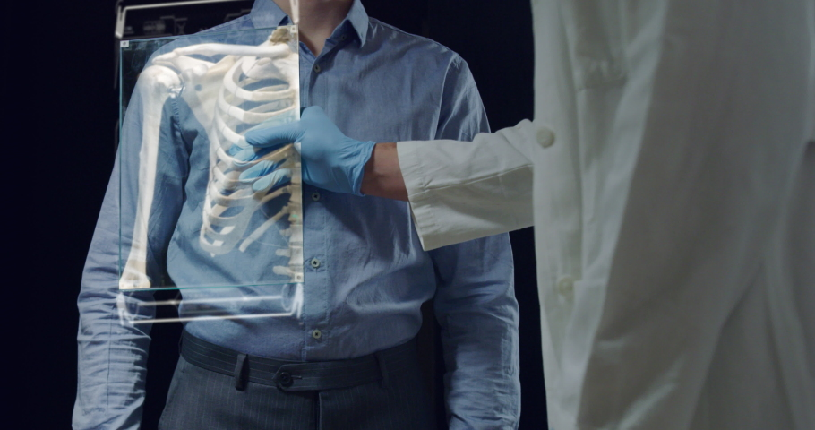 Slow motion of futuristic doctor is examining his patient's skeleton with newest technology scanning with augmented reality holograms in modern laboratory. | Shutterstock HD Video #1029921074