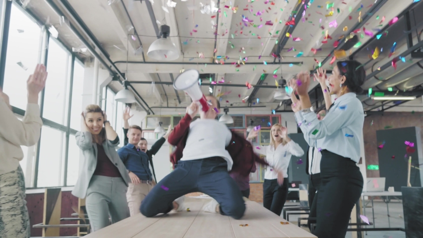 Manager start to dance on the table, sings into a megaphone, accelerates and slide on lap. Colleagues blow up flappers with confetti. Employees celebrate success. Corporate party business team | Shutterstock HD Video #1029925754