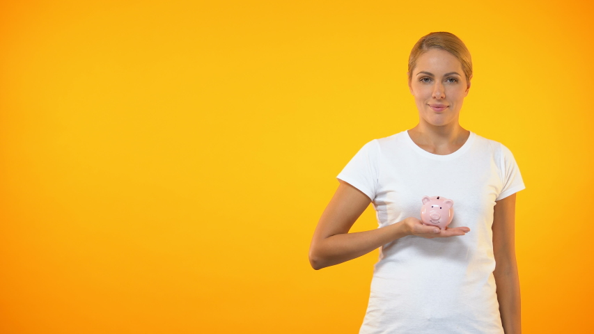 Positive female putting coin in piggybank, planning budget, financial savings   Shutterstock HD Video #1029942794