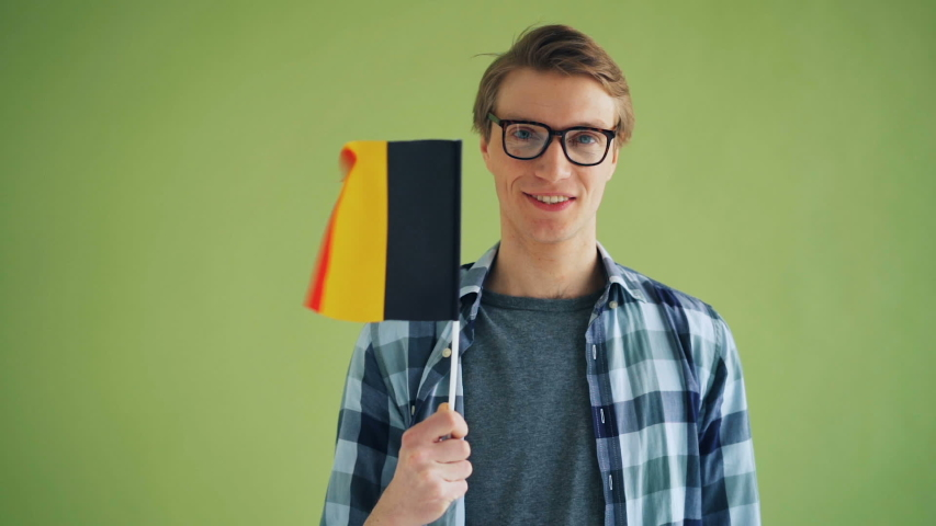 Slow motion portrait of cheerful person holding German flag and smiling standing on green background looking at camera. Millennials and countries concept.   Shutterstock HD Video #1029967364