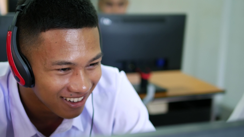 Asian high school male students wearing headphones are laughing and enjoying social media in computer class.   Shutterstock HD Video #1029995414