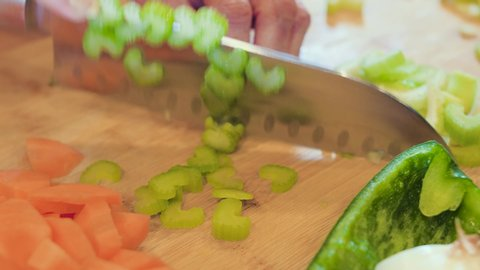 Closeup of woman slicing and dicing fresh green celery on wood cutting board. Female cook chopping vegetables with knife on wooden table.