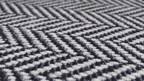 Herringbone fabric cloth close up background. Black and white tweed pattern, weaving, textile material.