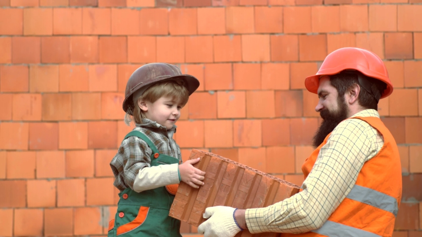 Child with her parent in Hard Hat Playing Building Blocks. Son helping her father build the wall. Little son bricklayer building a wall from bricks or stone blocks. Son helper   Shutterstock HD Video #1030042274