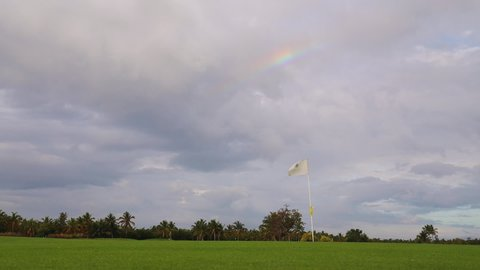 Tropical golf course and colorful rainbow over the flag