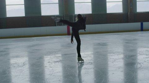 Slow motion of woman figure skating on ice skating rink while holding leg raised / Murray, Utah, United States