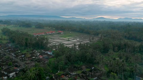 Slow rising aerial drone shot of rice fields and buildings surrounded by foggy woods. Cloudy weather just before the sun rises behind the mountain landscape. Ubud Bali, Indonesia