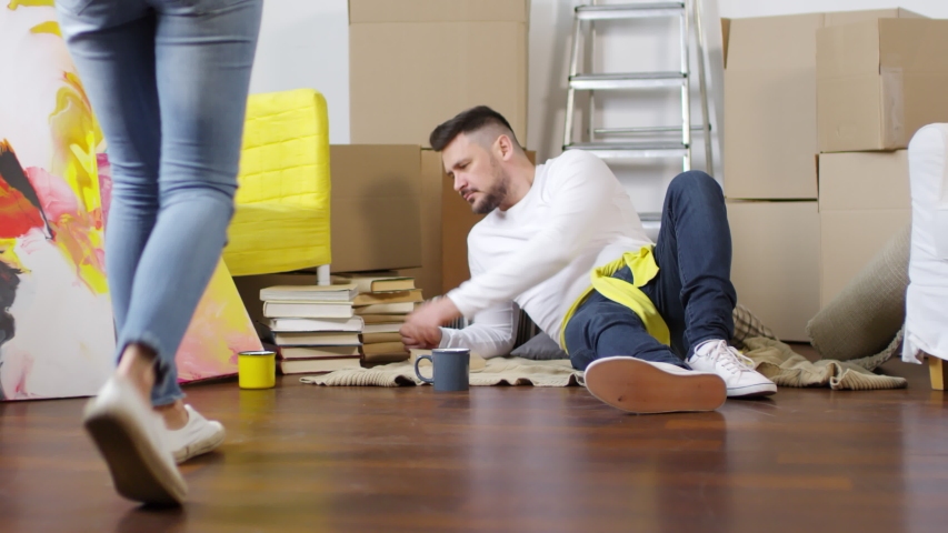 Dollying shot of happy Caucasian couple unpacking their possessions in new apartment, with wife bringing in cardboard box, sitting down beside her smiling husband and taking out framed pictures   Shutterstock HD Video #1030123304