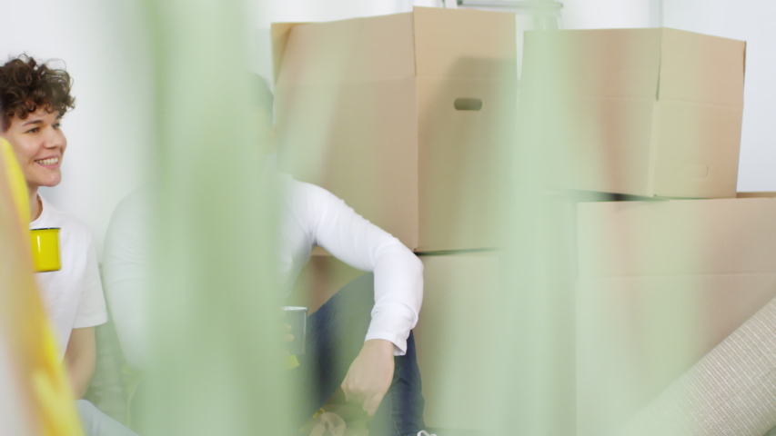 Panning thigh-up shot of happy young Caucasian couple relaxing in their new apartment after relocation, between cardboard boxes, drinking coffee, chatting and smiling with satisfaction   Shutterstock HD Video #1030126514