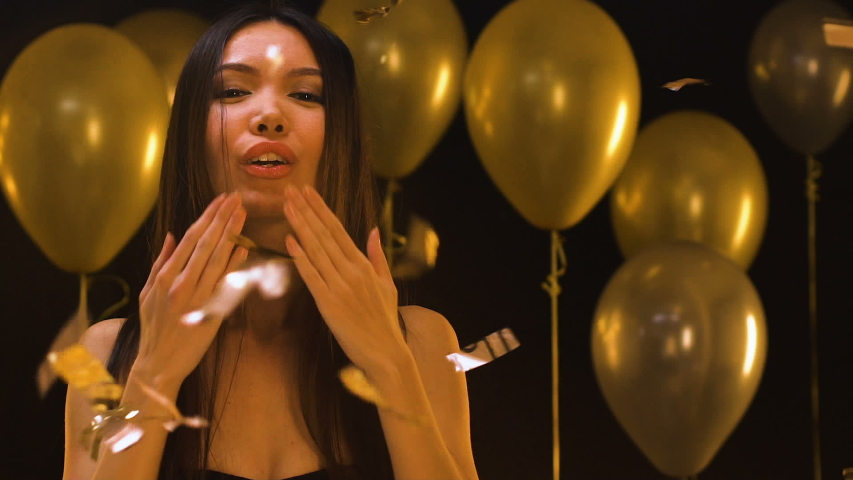 Attractive Asian woman sending air kiss to camera under falling confetti, party | Shutterstock HD Video #1030149734