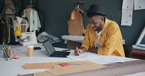 Male fashion designer African American guy is drawing new clothes using laptop creating fashionable garment sitting at table in studio. Work and art concept.
