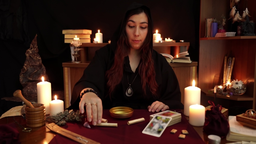 Witch is fortune teller in black mantle with rings read and burns magic spell. Tarot cards, amethyst stones, white candles on dark mystic background. Occult, esoteric, divination and wicca concept. | Shutterstock HD Video #1030171034