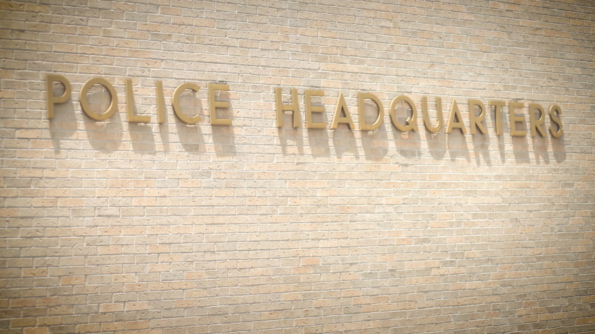 A police headquarters sign on a brick wall | Shutterstock HD Video #1030224614