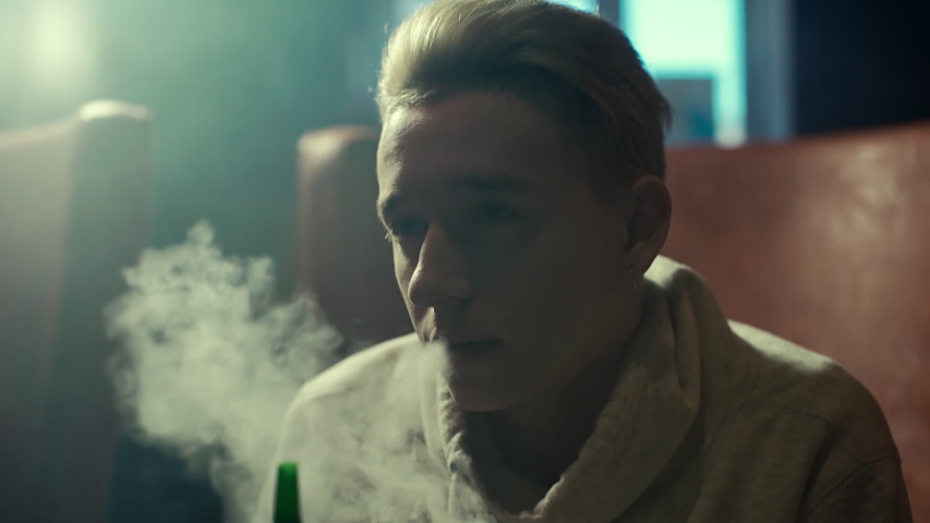 Close-up handsome blonde guy with an earring in his ear smoking a hookah in the dark hookah room in slow motion. Attractive young hipster man smoking hookah, communicating and relaxing with friends | Shutterstock HD Video #1030260464