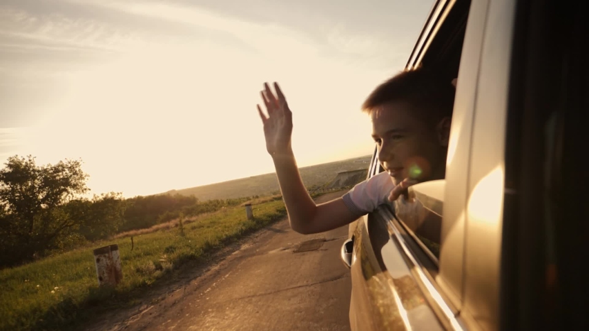 The boy looks out of the car window traveling the world. The boy's face in the sun with an arm stretched out of the car window. The concept of a happy family. Pursuit of travel and entertainment | Shutterstock HD Video #1030262264