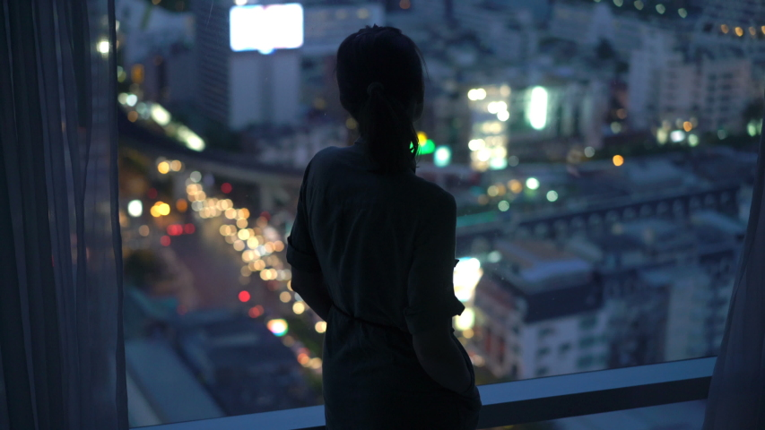 Silhouette of woman looking at city at night, standing by window at home   Shutterstock HD Video #1030263554