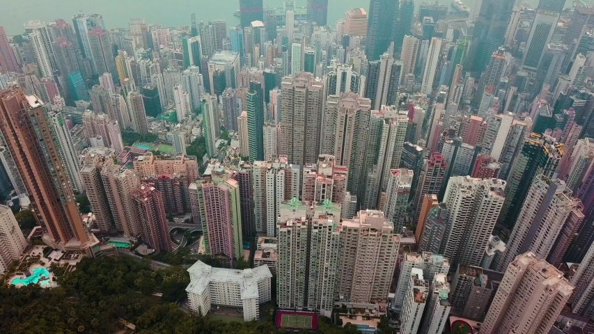 Aerial jib up of foggy Hong Kong cityscape and Victoria harbour