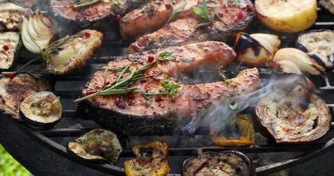Grilled fish, grilled salmon steak with the addition of rosemary, aromatic spices and vegetables on the grill plate outdoors, close-up, 4k. Grilled seafood