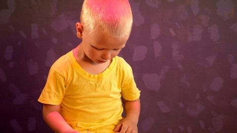 Little blond child is smiling and singing songs showing good mood. Yellow T-shirt and colored light from above emphasize tender children's emotions and joys. Concept of preschool education in family